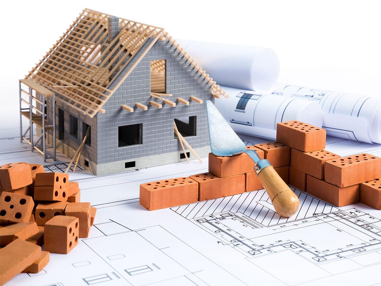 Modell eines Rohbaus mit Plänen, Maurerkelle, Ziegeln