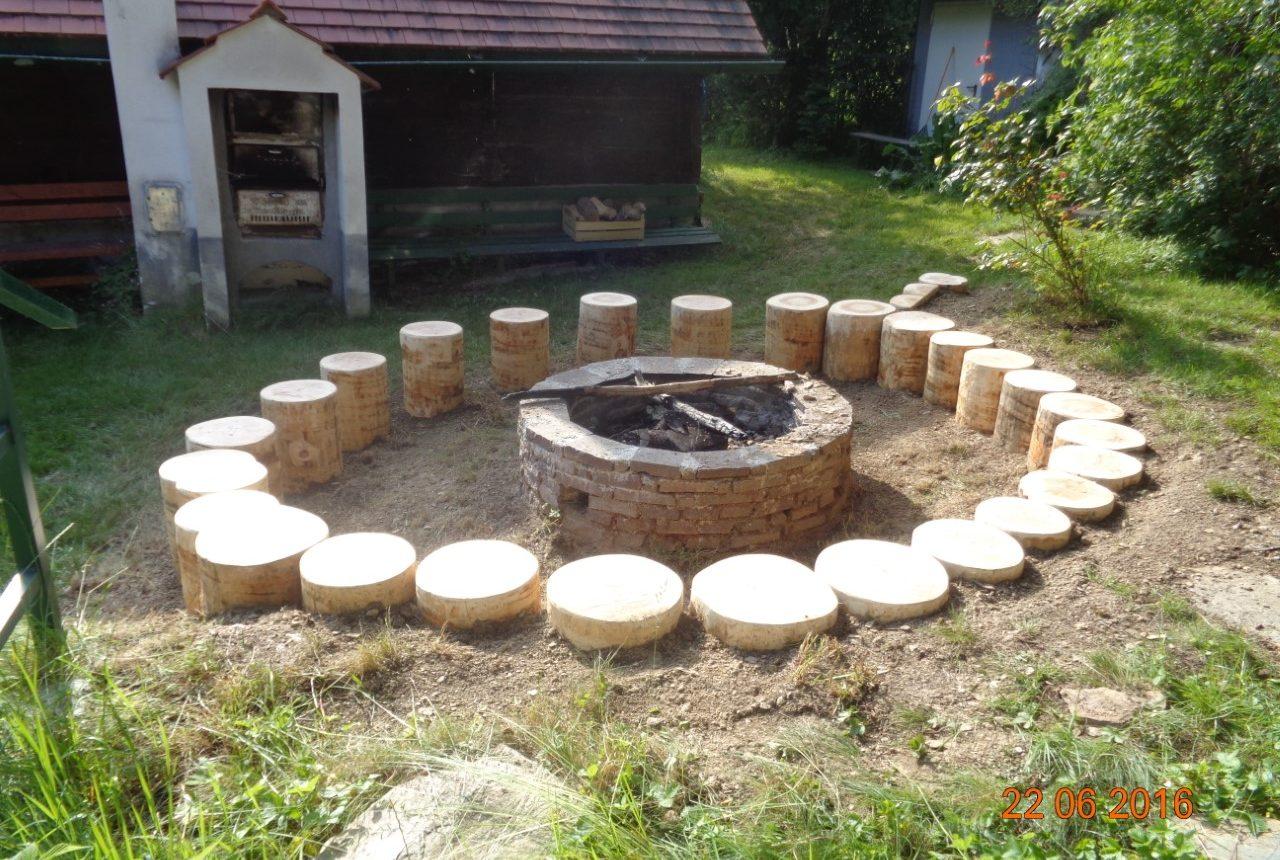 Gemütliche Feuerstelle für Lagerfeuer mit Baumstumpf und alten Ziegeln