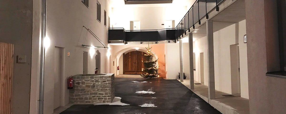 Beleuchteter Weihnachtsbaum im Innenhof von Kager Bau